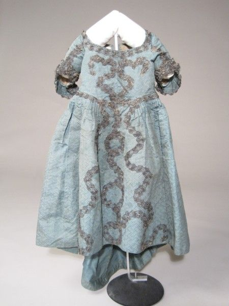 Child's Dress,1760-1770, silk/cotton. Light blue figured silk with woven design of latticed ribbons, the ribbons having a spot pattern. Back-fastening with trained skirt and leading strings. Squared neckline, pointed front waist. CB boned each side. Elbow length sleeves. Decorated with silver bobbin lace applied in serpentine patterns. See portrait by Johan Zoffany of George III & Queen Charlotte with 6 children, c.1770, for a very similar figured blue silk gown on one of the princesses.
