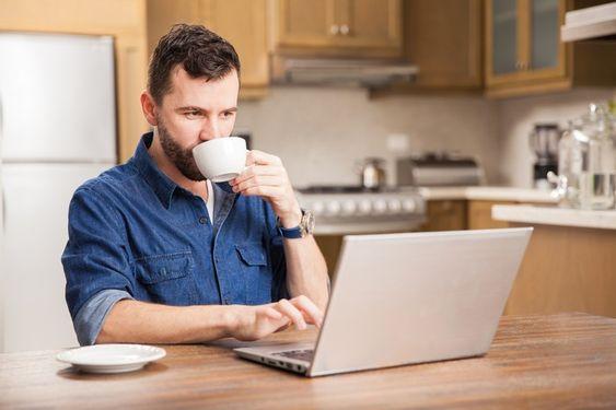 Mann, der auf Laptop in der Küche beim Trinken vom Becher tippt