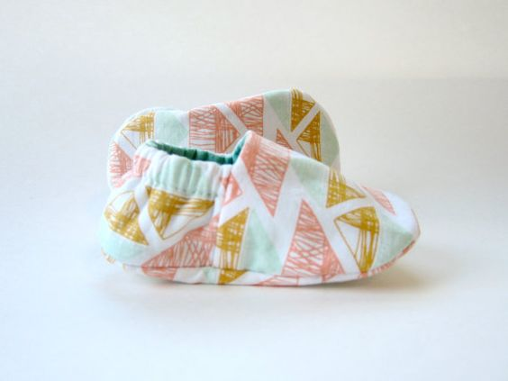 These little handmade baby booties are made with a pink, yarrow, aqua, and white triangle print cotton on one side and a solid aqua cotton on the other.