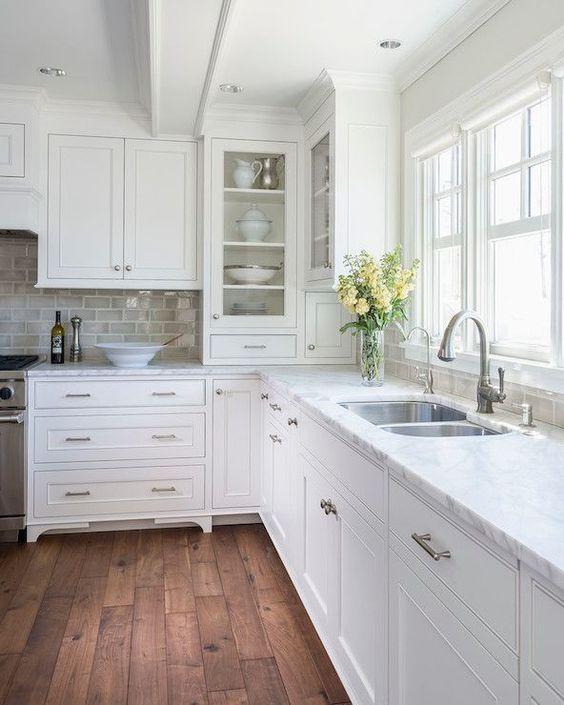 stunning light filled kitchen with inset white cabinets, medium toned, rustic hardwood floors, ceramic subway tile backsplash, marble counters