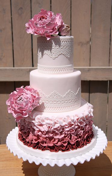 I loved peonies! These are made form gumpaste. The cake lace and fondant ruffles make this a fun wedding or party cake.