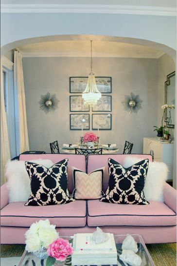 Gray walls, pink couch with black pillows.