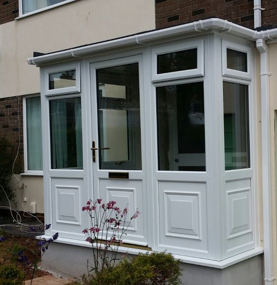 AGS Windows - Newton Abbot White PVCu Porch with felt roof, single door, and gold furnishing.