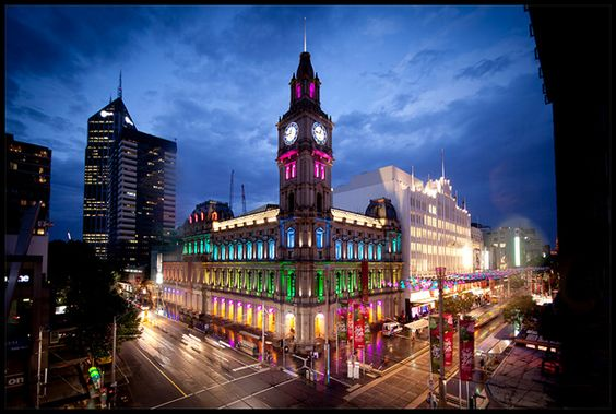 Melbourne's GPO building lit up in a rainbow spectrum by night.
