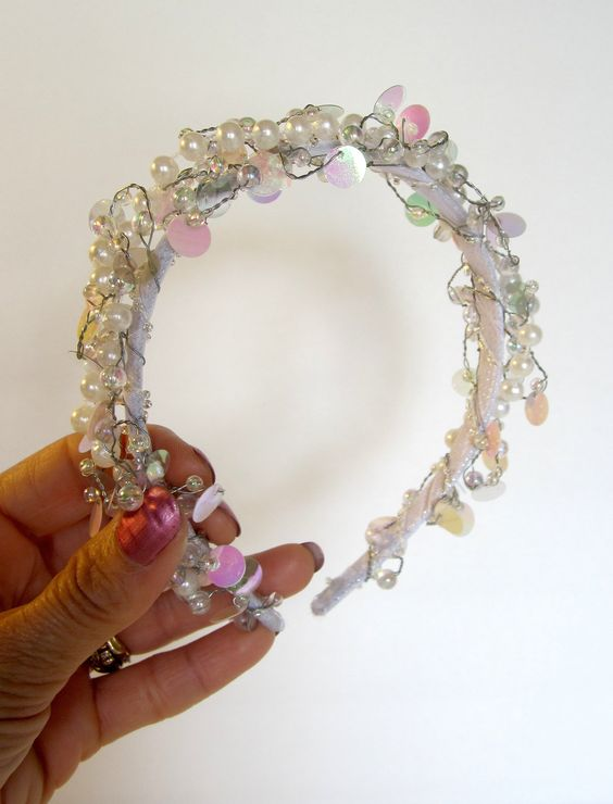 This is a sparkly, fun and fancy headband made with a wire garland of pearls and iridescent beads on a white headband base. It is perfect for the bride who wants a simple yet sparkly and fun headpiece, for the flower girl at a wedding, or just for the girl who loves headbands and loves to sparkle.