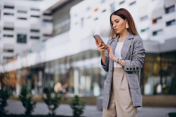 Mujer de negocios usando teléfono afuera en la calle por el edificio Foto gratis