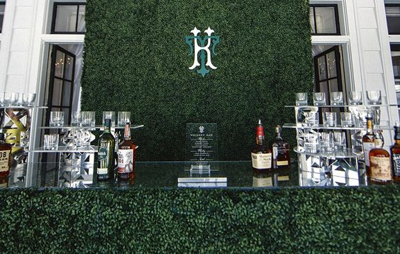 Sarah Allen Preston Designs created a custom monogram that hung behind the boxwood whiskey bar at this traditional wedding reception