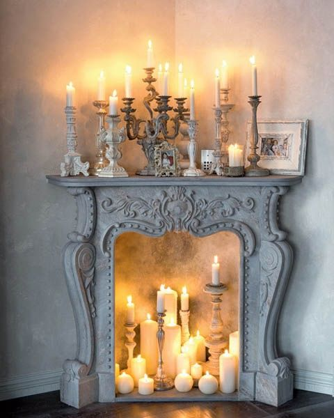 Elegant ornamental French stone fireplace filled with candles and candlesticks