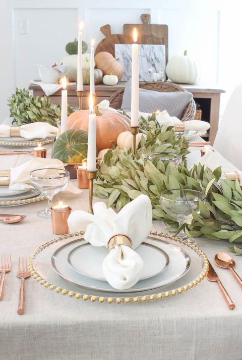 Brass and pastel make for an elegant Thanksgiving tablescape. White candles tucked into antique brass candlesticks, brass shot glasses that double as votive holders, a bay leaf garland and heirloom pumpkins cast a note of laid-back romance onto the holiday table.: