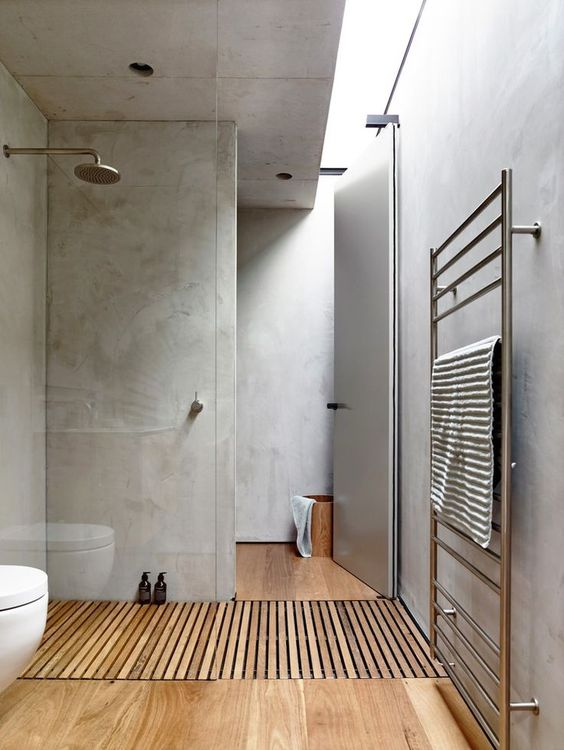 Natural wood tones warm up an otherwise industrial bathroom.