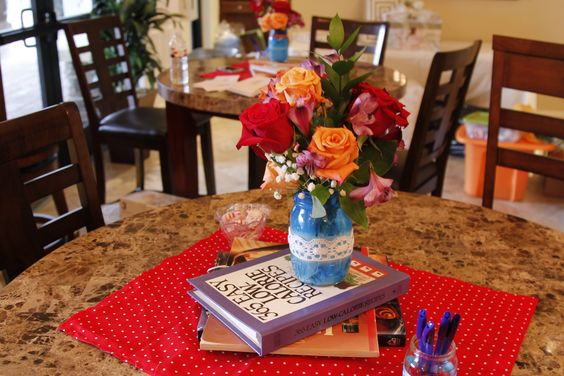 Centerpieces made with spray-painted mason jars + fresh flowers sitting on vintage cookbooks.
