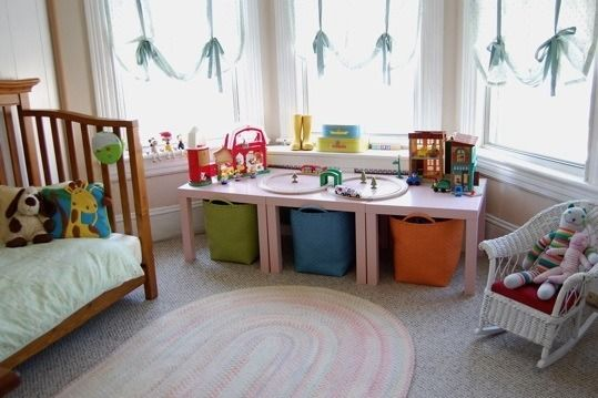 Three tables together with bins under to hide toys.