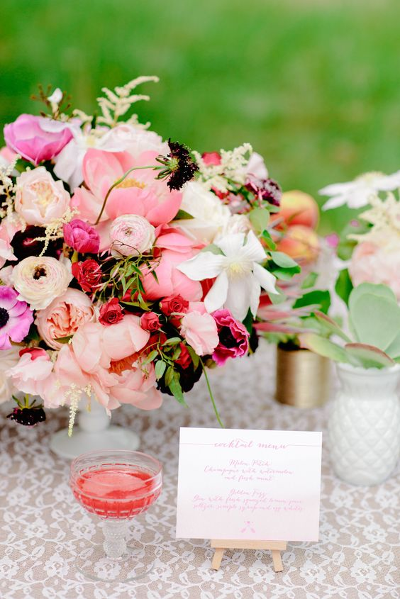 Vibrant, lush floral arrangement in shades of peach and pink. #wedding #flowers #centerpiece