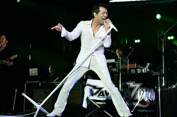 上下白い衣装を着て白いスタンドマイクを握っている矢沢永吉の画像
