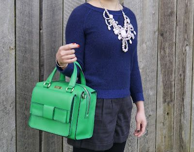 A statement necklace and bright green bag dress up a neutral outfit.
