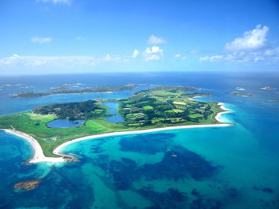 Arial view of Tresco on the Isles of Scilly approaching from the south-east. You can see the Great Pool with the Abbey and Gardens on it's edge.  The long beach is Pentle.