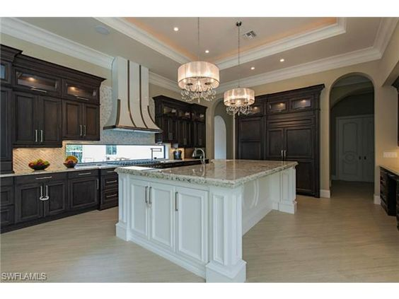Custom kitchen with huge center island.  White and dark contrast cabinets and twin chandeliers.  By Imperial Homes.  Brynwood Drive in Quail West | North Naples, Florida
