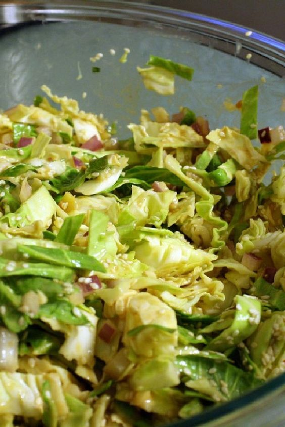 Recipe including course(s): Salad; and ingredients: almonds, black pepper, cabbage, garlic, ginger root, green onion, rice vinegar, salt, sesame oil, sesame seeds, sugar