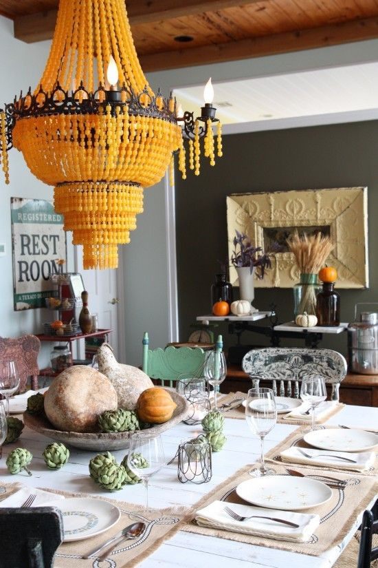 unbelievable awesome yellow glass bead iron chandelier, dark grey wall, mismatched flea market chairs, gourds as a centerpiece, repurposed vintage tin ceiling tile mirror, artichokes on the table, fall table decor
