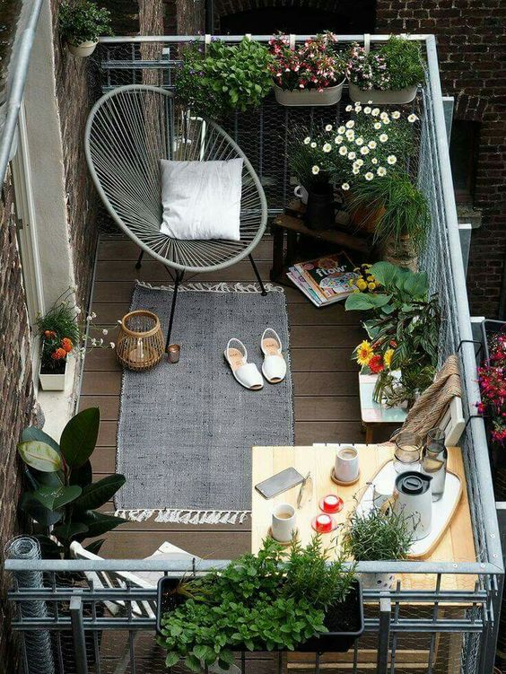 You can make a small balcony feel cozy by installing some hanging planters, a comfy seat and a small rug.: