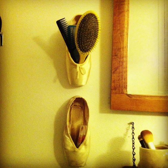 """I finally came up with something to do with my old pointe shoes! Re-purpose them as little wall containers! Here I've used one to hold some combs and a hair brush & one to hold my lip gloss. This would also work really well for pens/pencils/office supplies, hair accessories, etc....If you aren't a dancer but you like this idea, try going to a dance supply store. They often have """"bargain boxes"""" with pairs of pointe shoes for super-cheap (as low as $5 or $10), and the sizes are usually really…"""