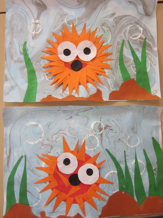 "Year 1 did a workshop where we read the book ""Barry the fish with fingers"" and did a collage about the Puffer fish. Marbling the background., printmaking on the bubbles and collage for the Puffer fish, seaweed and rocks."