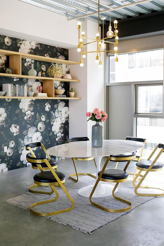 Feminine workspace with floral wallpaper, a gold chandelier and gold chairs: