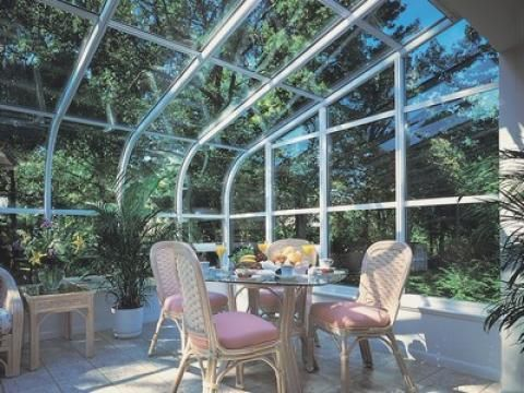 Traditional Sunroom with light red cushioned dining chairs