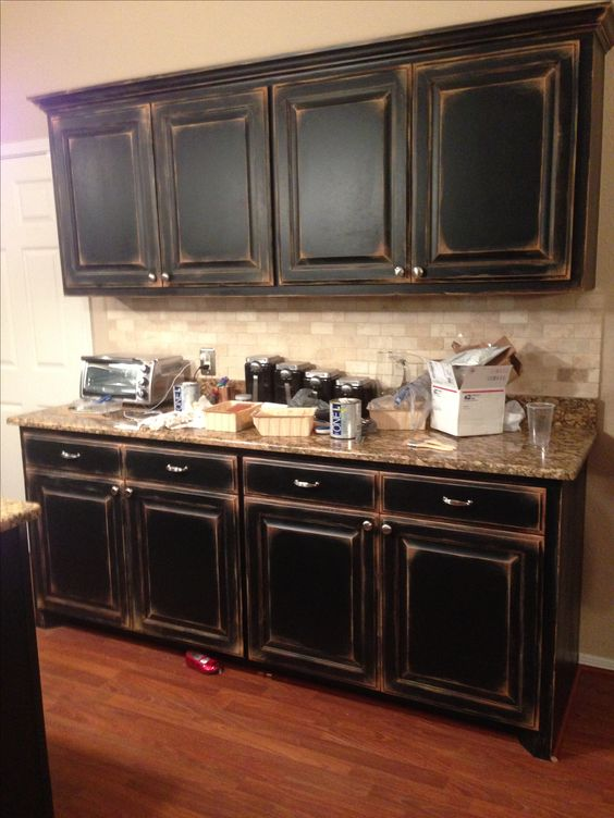 Black cabinets with faux distressing. Used 3 different colors of flat paint to create this super distressed look. Love the dingy black. DIY success.