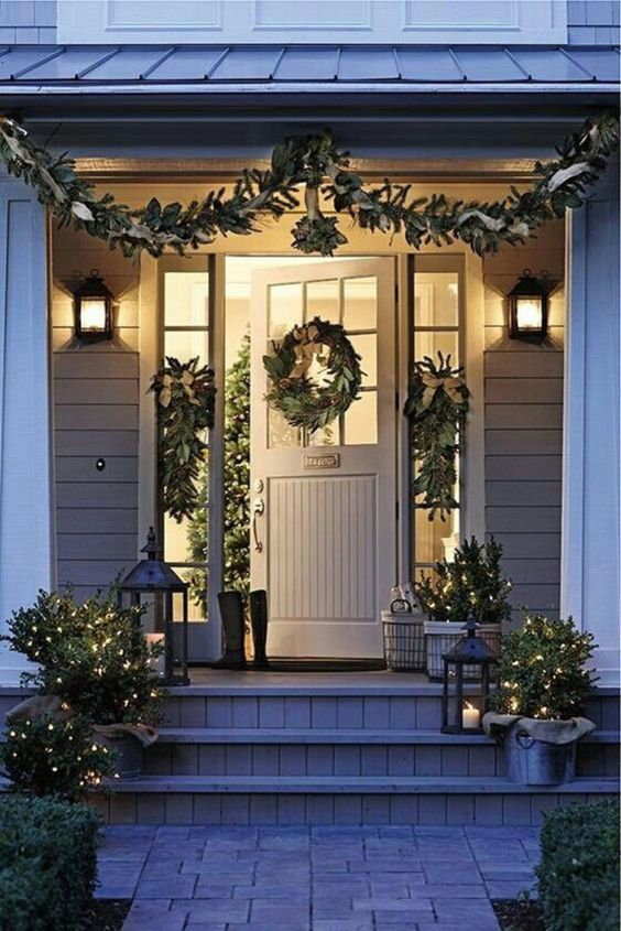 Christmas front door with beautiful wreath, garland, mistletoe, and white lights