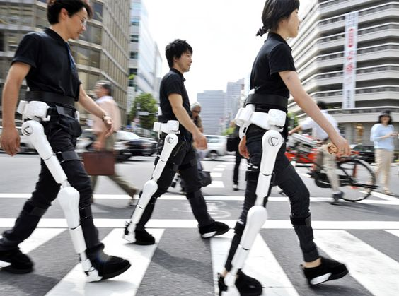 Japan's robotics venture Cyberdyne employees wearing a robot-suit known as HAL (Hybrid Assistive Limb) walk on a street in Tokyo