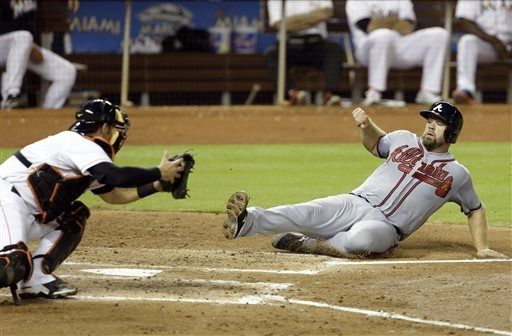 Atlanta Braves' Evan Gattis, right, beats the throw to Miami Marlins catcher Jeff Mathis, left, to score on a single by Chris Johnson in the fourth inning during a baseball game, Monday, Sept. 9, 2013 in Miami.