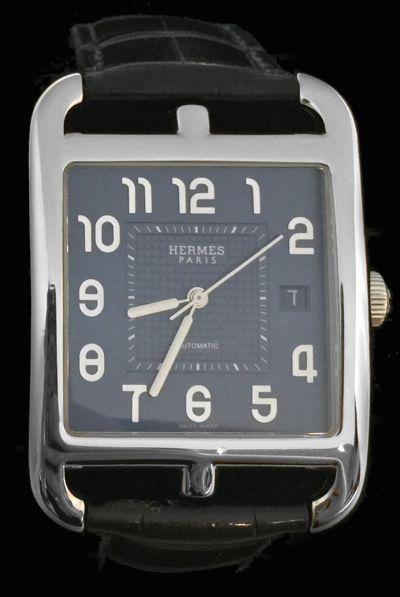 Une montre signée de la Maison Hermès en acier modèle Cape Cod sur un bracelet en cuir avec sa boucle déployante en acier.   Cadran bleu-gris, date à trois heures.   Mouvement automatique.   Très grand modèle.   Largeur cadran : 35 mm.  Longueur cadran : 34 mm.   Prix du neuf : 4 600 €.