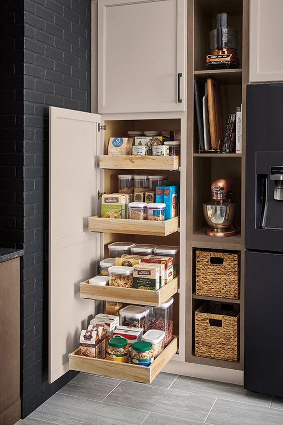 A tall pantry with roll-trays makes achieving a well-organized kitchen a breeze. Click to discover more smart ways to organize your kitchen cabinets.