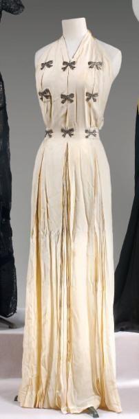 Jean PATOU Robe longue en crêpe écru, encolure américaine sur profonde circa 1935 / 1938  Robe longue en crêpe écru, encolure américaine sur profonde échancrure aux emmanches, buste à trois soufflets creux brodés de noeuds en strass, jupe à trois soufflets plissés soleil, dos reprenant l'échancrure et le plissé soleil, souligné d'une ceinture à nouer (taches) Griffe blanche, graphisme rose Nous y joignons une jupe en satin écru sans griffe.