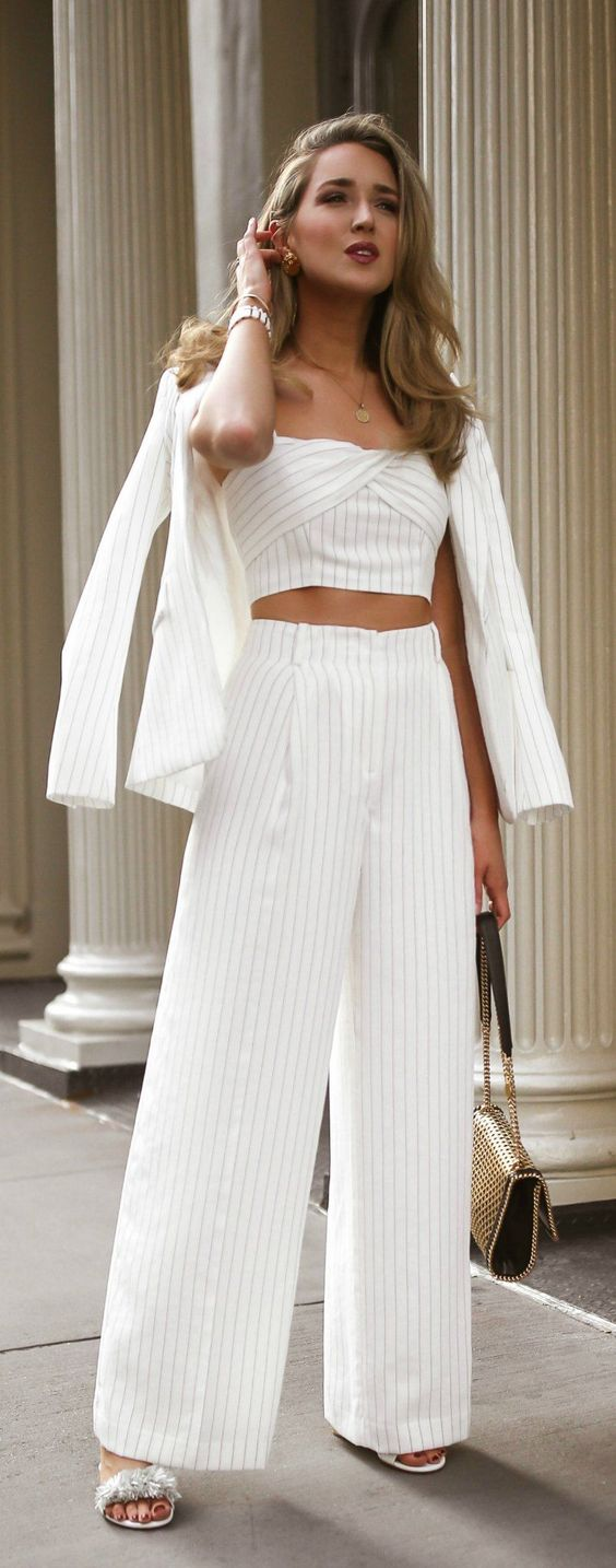 Matching three-piece and all white? Yes please // White pinstripe suit with coordinating twist-front crop-top + high-waist pleated wide-leg pants, white slide sandal shoes with ruffle details, gold statement earrings, stacked gold bracelet, woven faux leather flap shoulder bag {Rachel Zoe, Stella McCartney, Roxanne Assoulin, classic style, monochrome dressing}