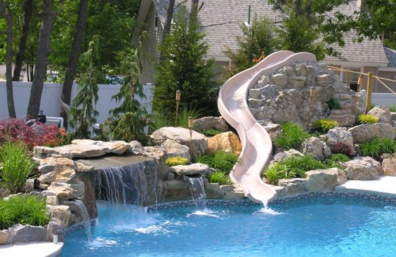 Custom rock waterfall with water slide from pool town in for Swimming pools with slides and waterfalls