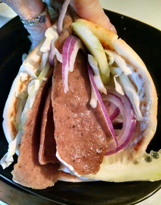 Homemade Gyros... Warm pita bread, Greek sour cream, angel hair cabbage, red onion, cucumber, gyro meat, and feta cheese...!!