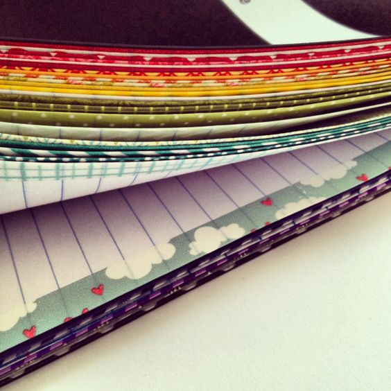 Upgrading a cheap composition notebook by attaching washi tape to the edges of the pages. Attach pages in groups of three for increased sturdiness.