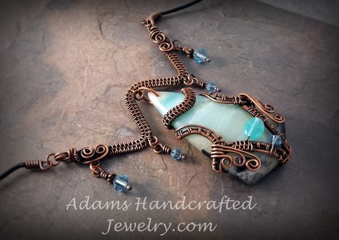 Amazing Amazonite Pendant Necklace in a lovely light sky blue color. It has been wire-wrapped in a copper patina finish with an original design and has five beautiful Swarovski crystals and one Czech glass bead  to accent it. It has a delicate bar above the pendant. Included is a 20 black round leath
