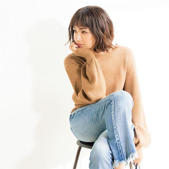 茶色いニットにデニムを履いて座っている佐田真由美の画像