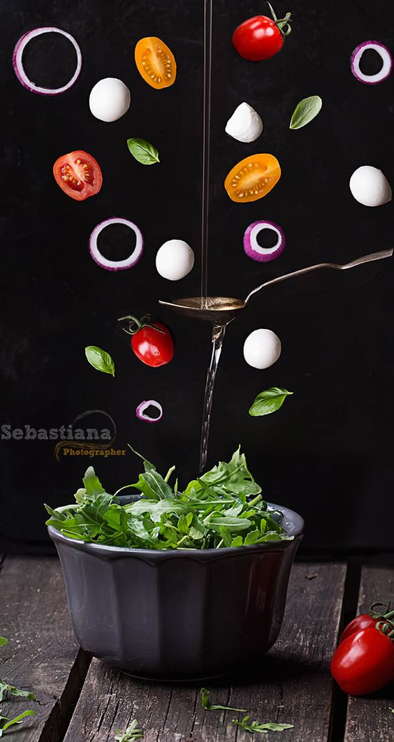 Flying Salad - Ruccola Mozzarella and tomato salad with flying ingredients basil, onion, olive oil in vintage spoon