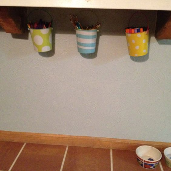 Hanging kids art supplies in buckets under the breakfast bar keeps them organized and within reach!