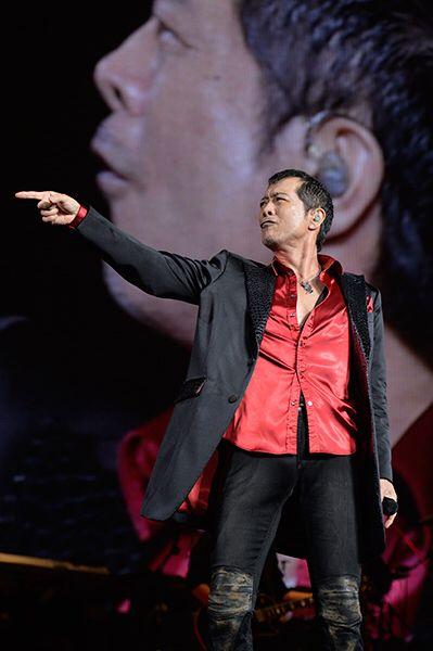 赤いシャツに黒いジャケットを着て指をさしている矢沢永吉の画像