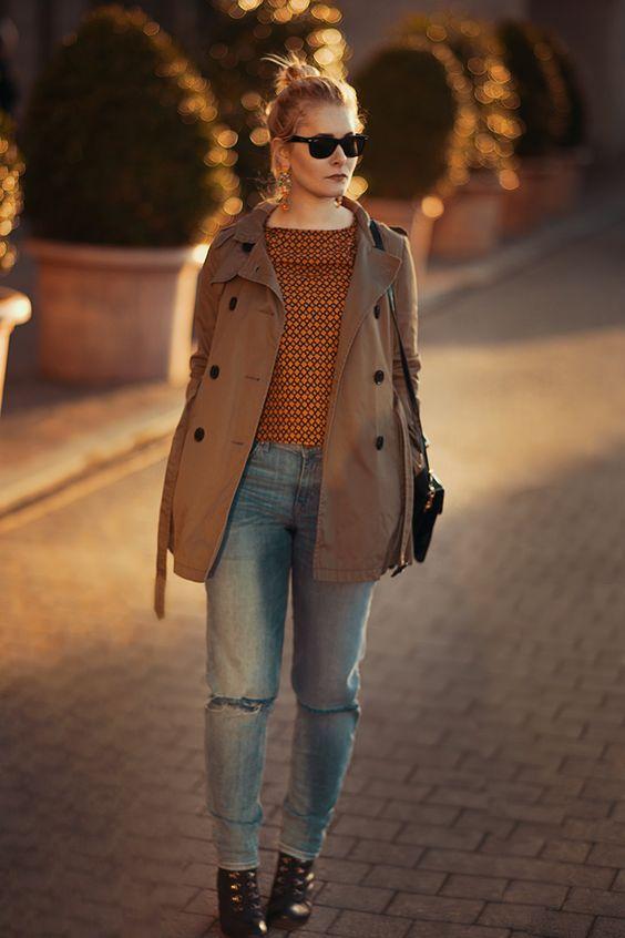 Christina Key trägt einen coolen Herbstlook mit einem khaki farbenen Trenchcoat, einer hellblauen Boyfriend Jeans und einem orangenen Retro Bluse