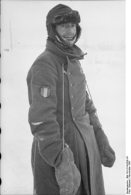 Eastern Front, Nov 1941: French volunteer belonging to the French Legion fighting on the side of the Germans against Bolshevism. Just like his German comrades, this Frenchman has just an overcoat to defend against the polar Russian coat. He has connected his mittens to the top of the coat with string, lest he loses them.The fur cap with ear protection is a most welcome addition to his kit.