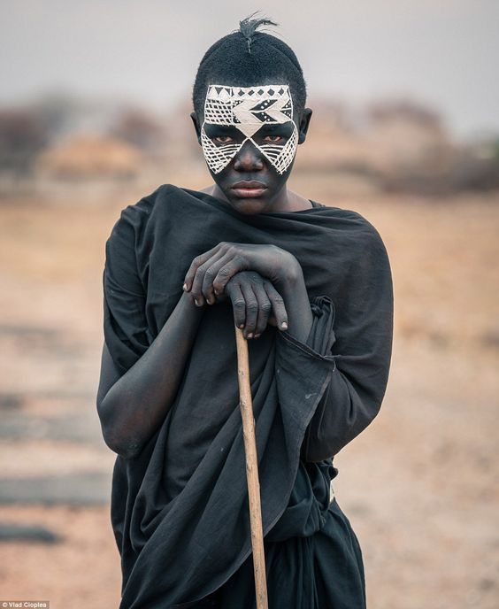 Dressed from head to toe in black, with white markings on his face, this is a Maasai nomad known as a Nyangulo. He is undergoing a tribal trial in which he must live in the wild for three months