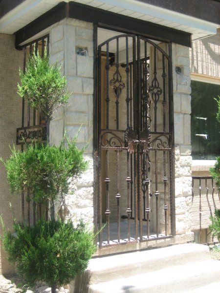 Outdoor Foyer Ideas : Iron front portico gate creates an outdoor foyer and