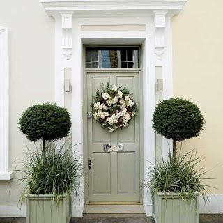 Gorgeous greyed sage door (try Farrow and Ball French Gray for similar) flanked by two half-standard topiary trees and a pretty wreath on the door