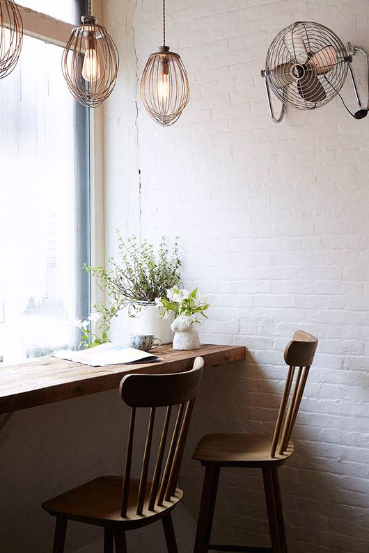 Window seat at Maman in Manhattan. Wooden bar table, wooden chairs, whisk pendant lights, pretty foraged bouquets, painted white brick
